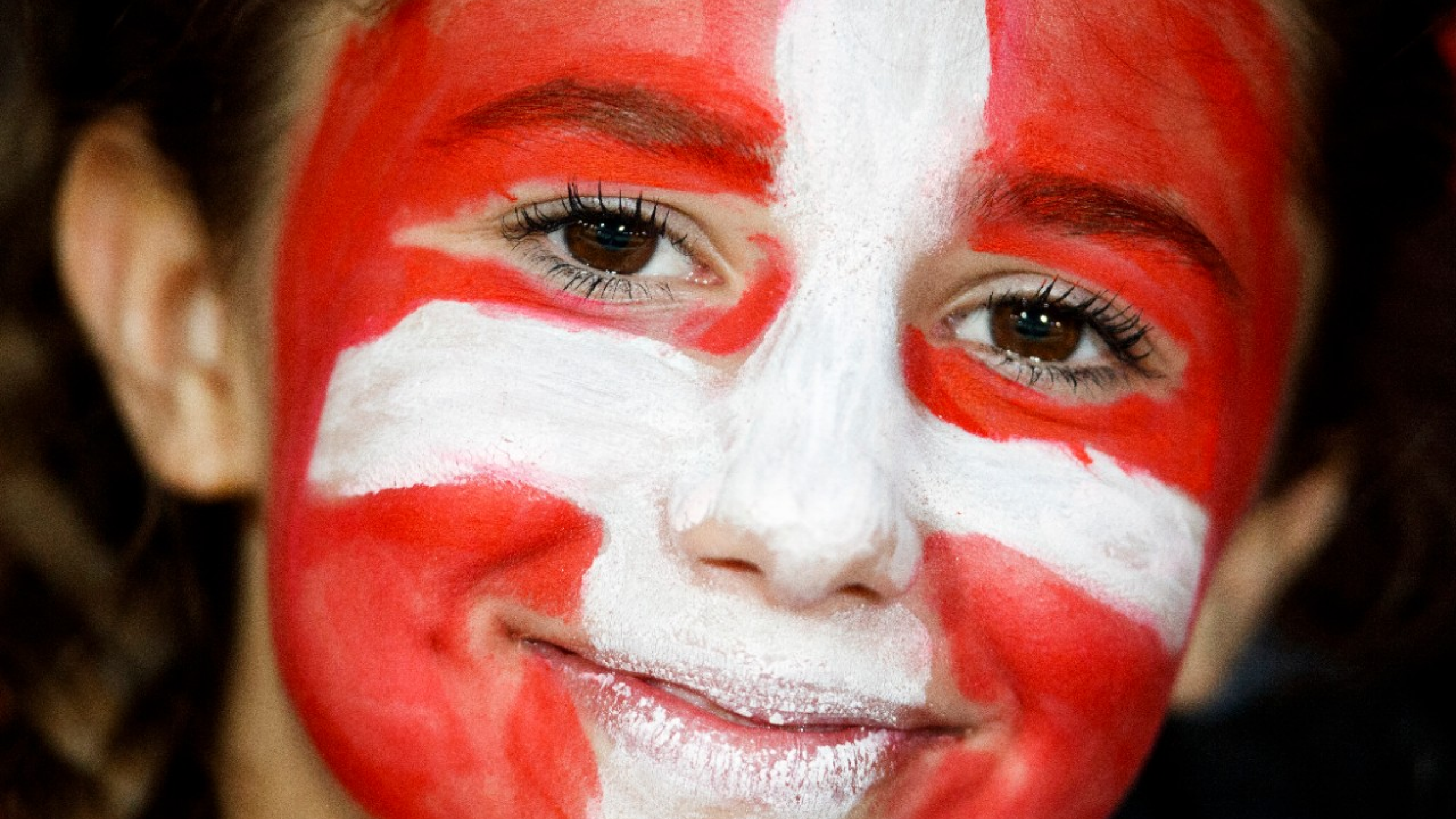 A young fan with Swiss flag makeup smiles during a friendly soccer match on the side line of the 2018 Fifa World Cup group B qualification between Switzerland and Belarus at the Stadium Maladiere, in Neuchatel, Switzerland, Thursday, June 1, 2017. (KEYSTONE/Valentin Flauraud)