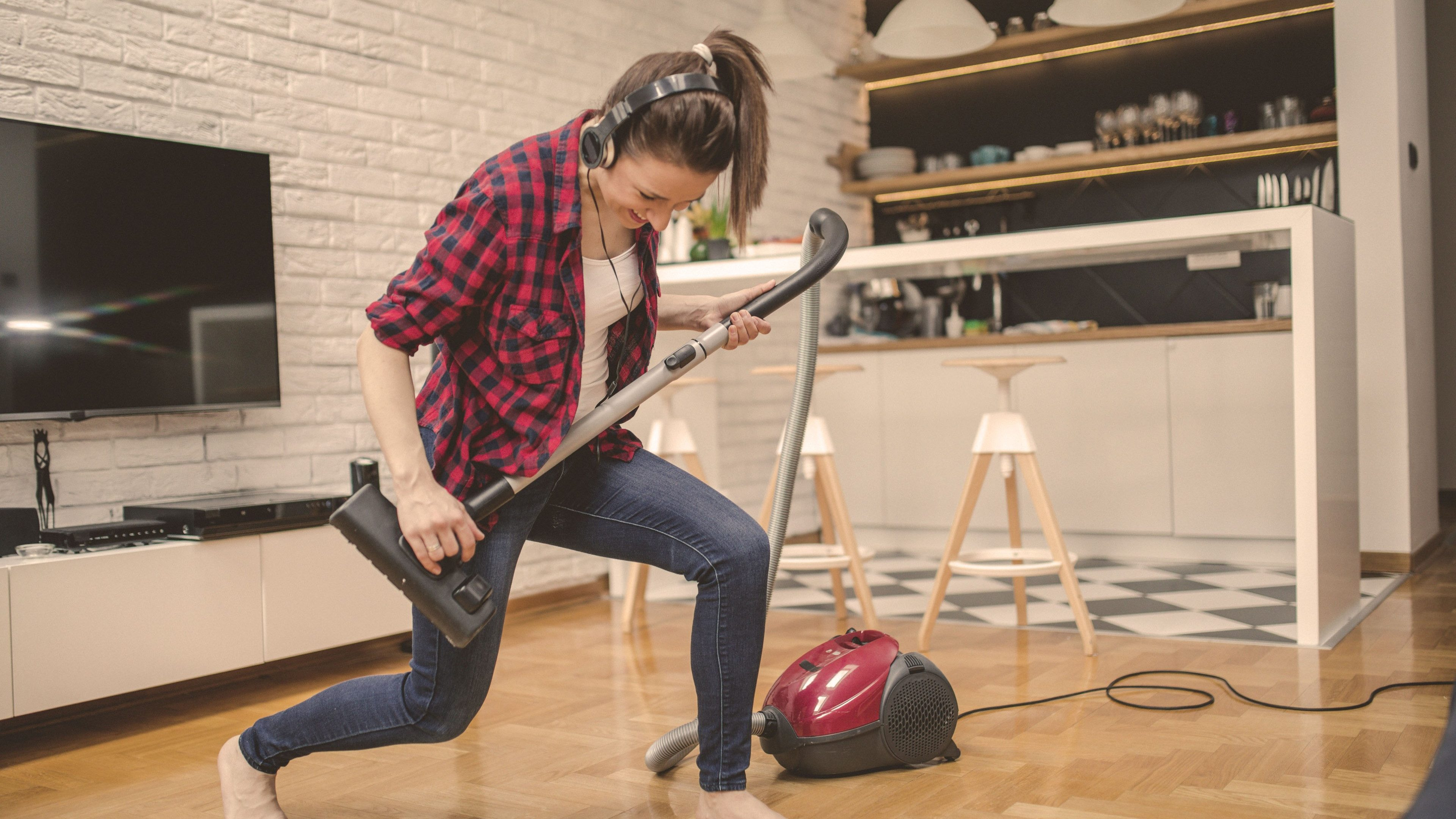 Young woman using vacuum cleaner to clean her house and listening music and playing imaginary guitar