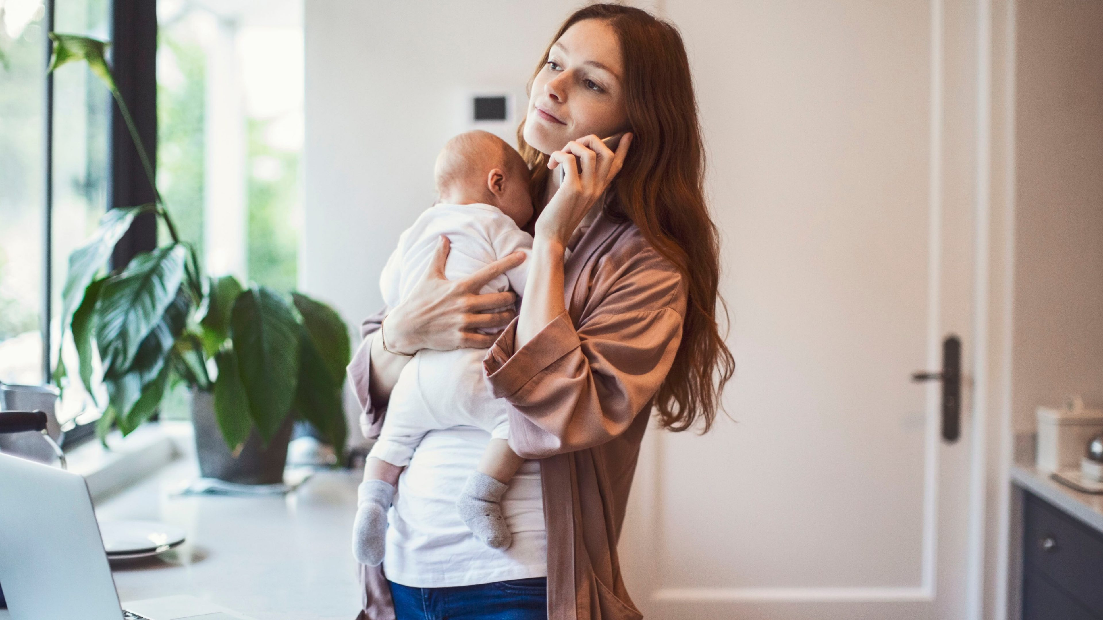 Woman using mobile phone while carrying baby at kitchen counter. Mid adult mother is with newborn boy standing at home. She is wearing casuals.