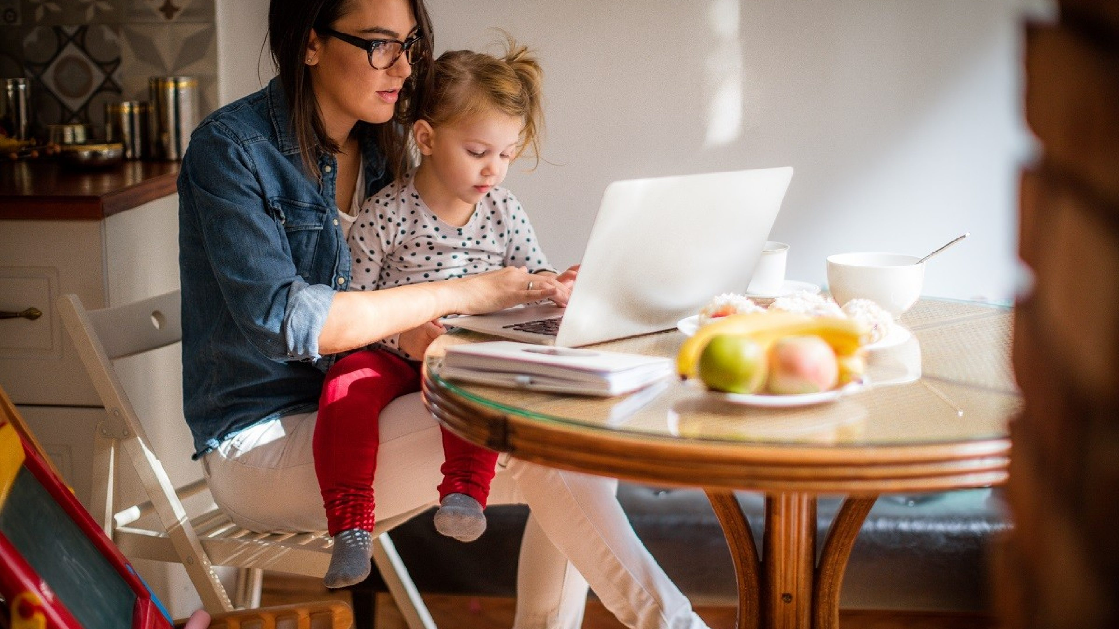 Photo of a little girl trying to help mom who is working on a computer at their dining table