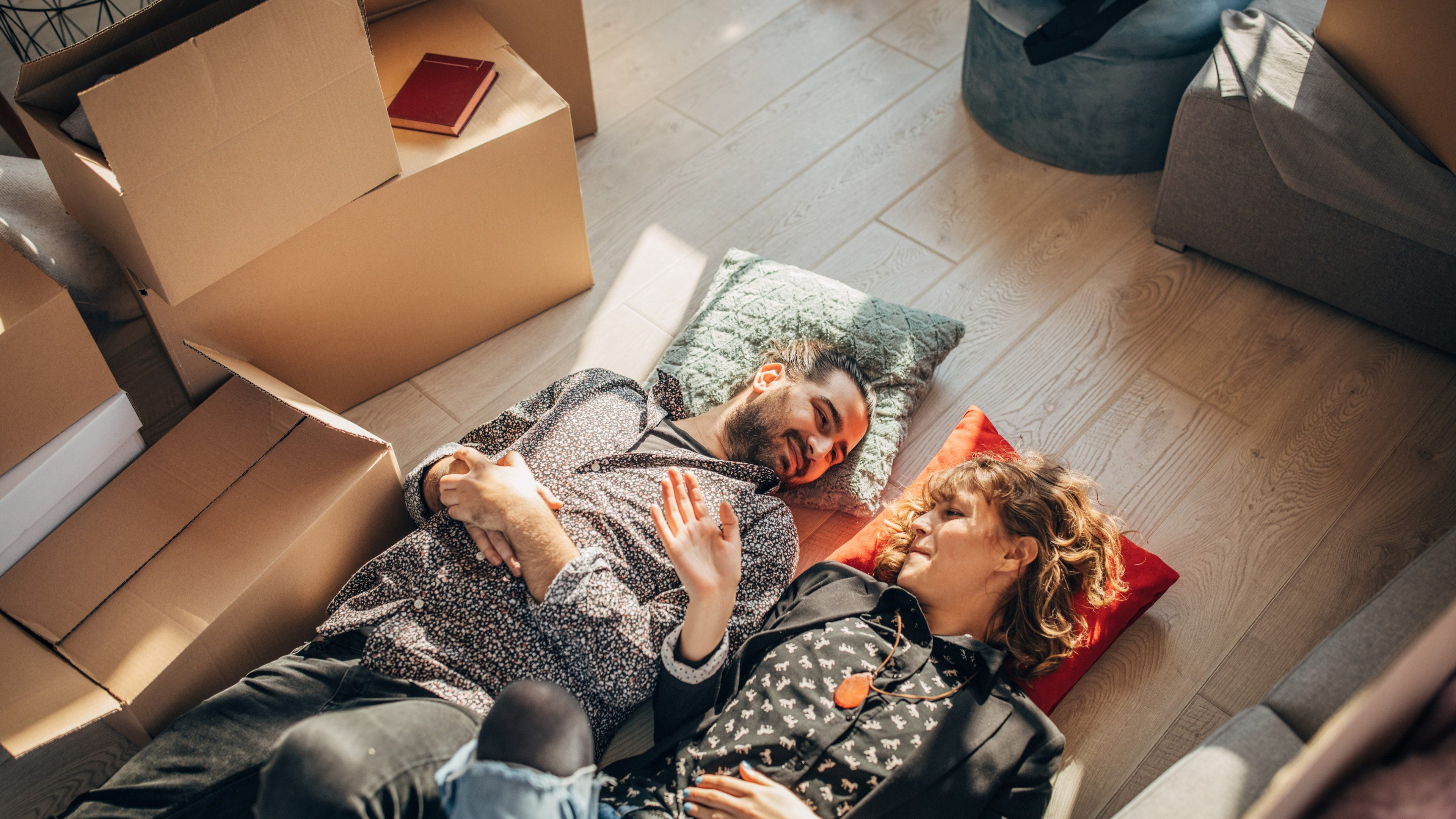 Man and woman, young couple moving into their new apartment together, lying on the floor together.