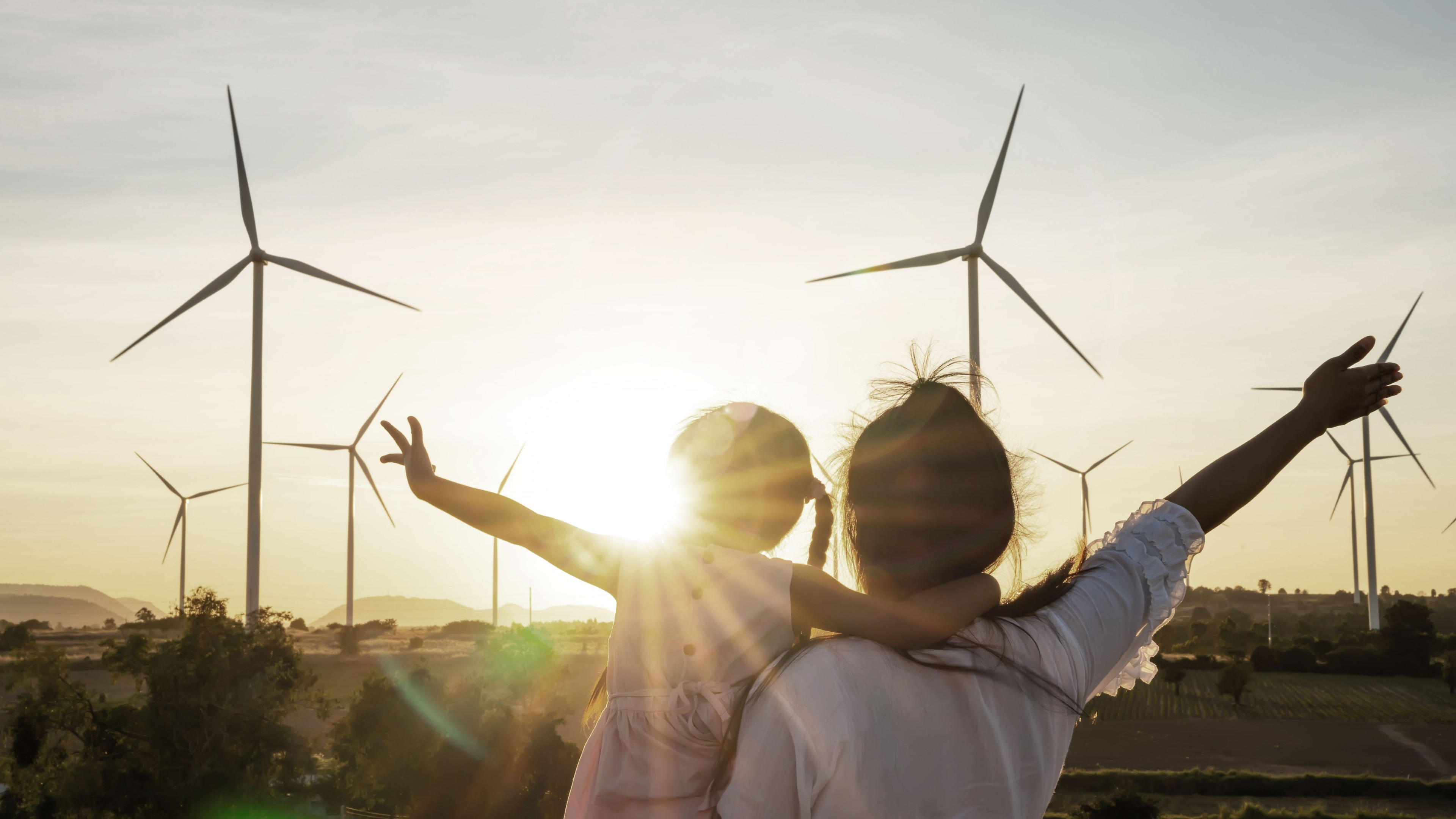 Bearded man in glasses kneeling on floor and catching ball while teaching boy to play football in cozy room at home