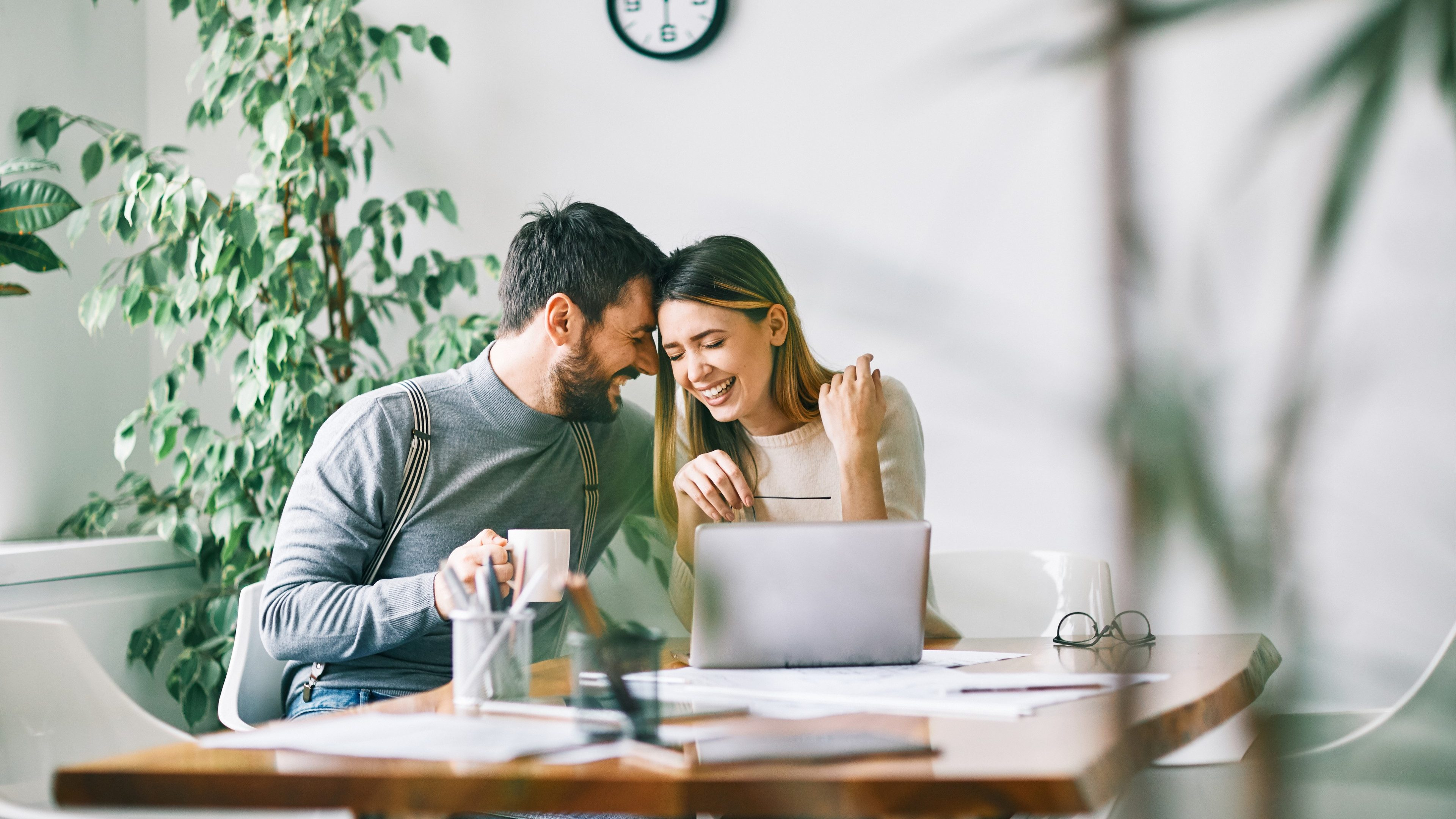 Smiling couple working at home or in the office with laptop
