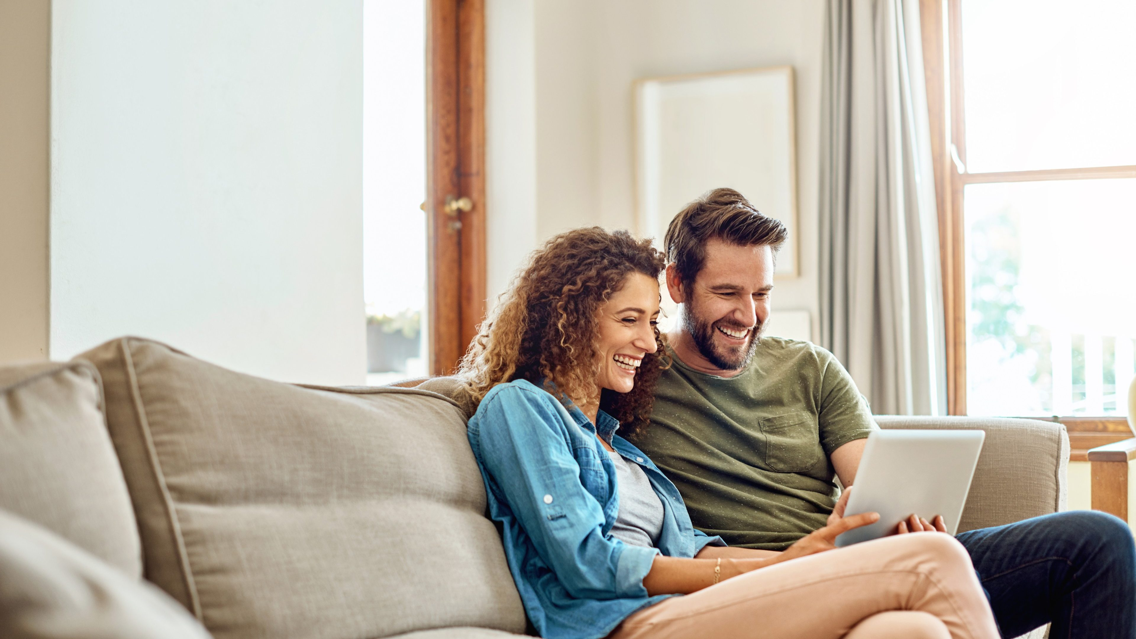 Shot of a happy young couple using a digital tablet together on the sofa at home