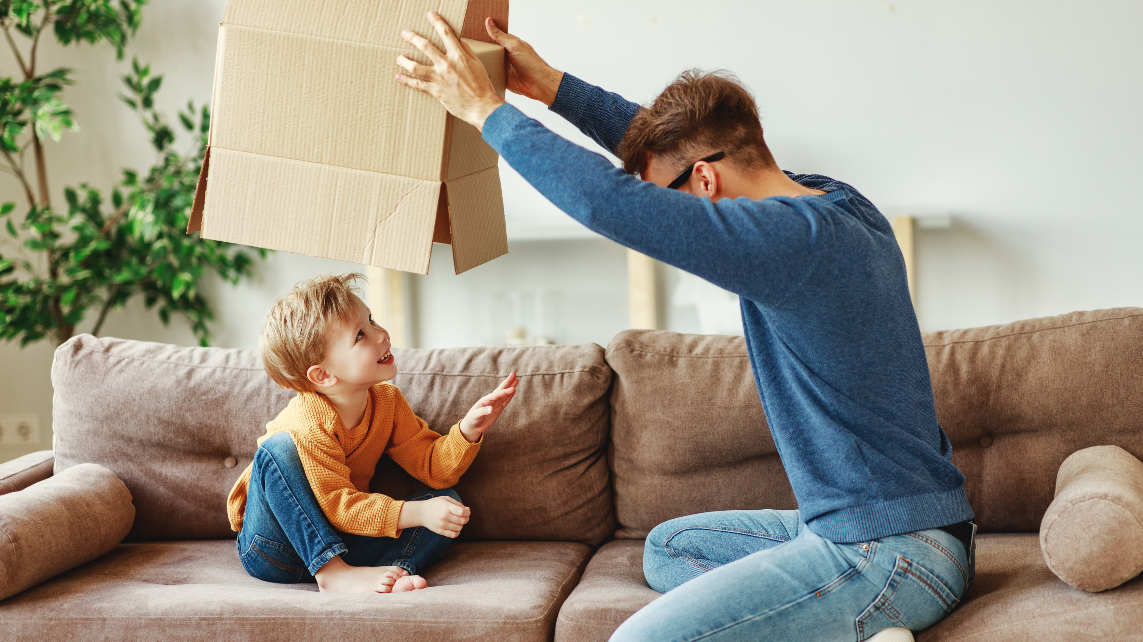 Side view of adult man lifting carton box over smiling boy while sitting on sofa and playing at home together